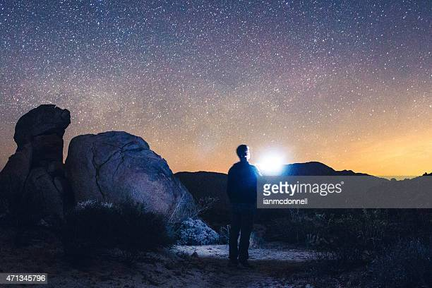 Man alone in the dessert with starry sky in the background