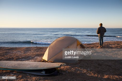 Man Alone on Beach with Tent and Surfboards