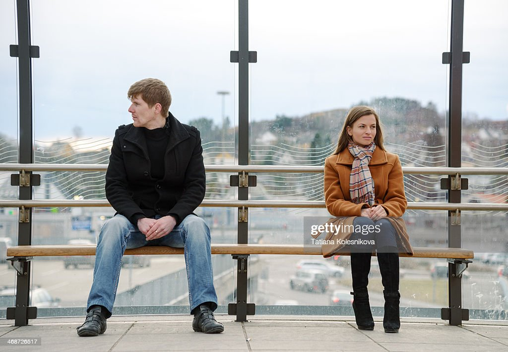 Man amd woman sitting far apart on a bench.