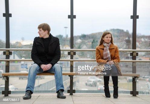 Man amd woman sitting far apart on a bench.