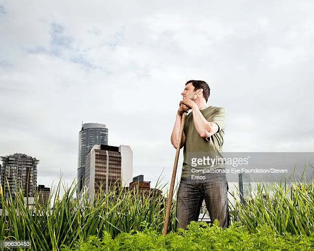 man amongst greenery with skyline in background