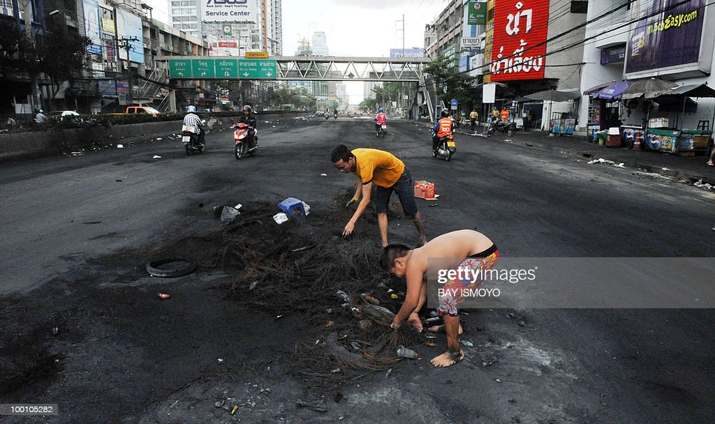 A man and a boy collect iron wires from the burnt tires on Rama IV street in downtown Bangkok on May 21, 2010. Thailand picked up the pieces after violence and mayhem triggered by a crackdown on anti-government protests, as the focus swung to recovery and reconciliation in a divided nation. AFP PHOTO / Bay ISMOYO