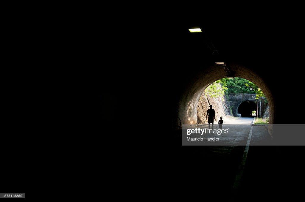 A man and a boy in a World War II era tunnel in Ogasawara Village.