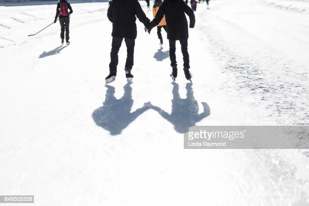 A man and a boy skating hand in hand on a ice rink