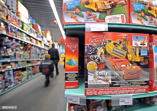 A man and a boy walk past the shelves of La Grande Recre toys departement store in the French northern city of BruaylaBuissiere on November 20 2010...