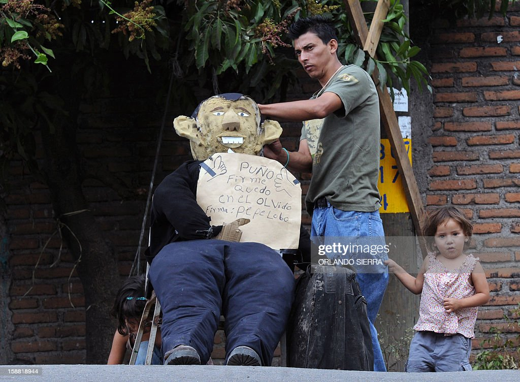 A man and a child arrange a rag doll depicting Honduran President Porfirio Lobo, on December 30, 2012 in Tegucigalpa. Hundurans burn rag dolls to see the 'Old Year' off. AFP PHOTO / Orlando SIERRA