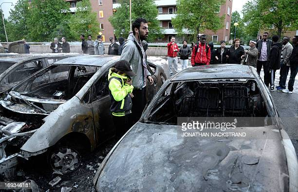 A man and a child look at the scene where cars stand gutted by fire in the Stockholm suburb of Rinkeby after youths rioted in several different...