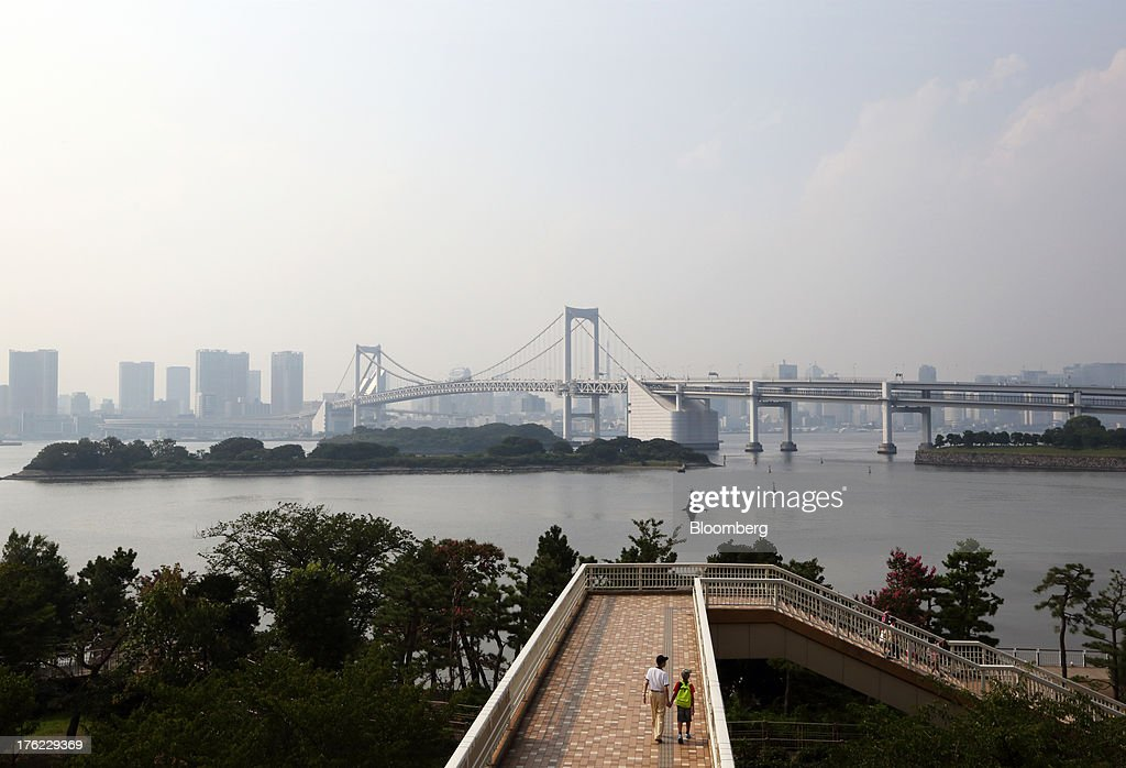 A man and a child walk along a pedestrian overpass across from the Rainbow Bridge in the Odaiba area of Tokyo, Japan, on Monday, Aug. 12, 2013. Japan's economy slowed more than forecast in the second quarter as businesses cut investment, undermining gains in consumer and government spending that helped reduce deflationary pressures. Photographer: Tomohiro Ohsumi/Bloomberg via Getty Images
