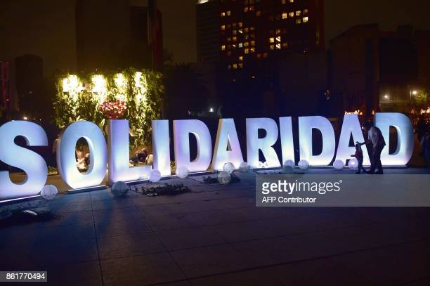 TOPSHOT A man and a child walk in front of letters that form the word 'Solidarity' during a tribute to the victims of Mexico's last earthquake at the...
