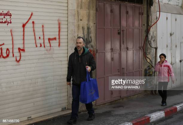 A man and a child walk past closed shops in Jerusalem as a general strike was called following US President Donald Trump's decision to recognise...