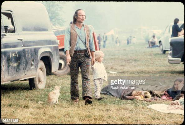 A man and a child walking past people in sleeping bags at the Woodstock music festival August 1969