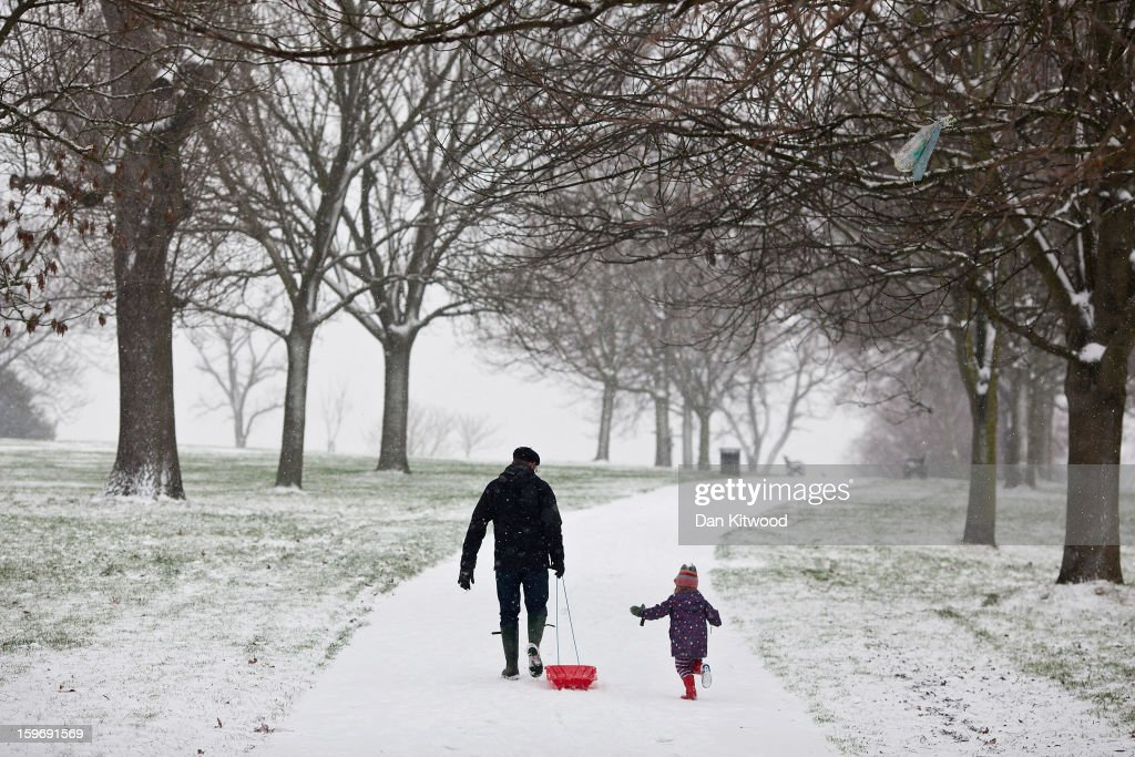 A man and a little girl pull a sledge up a hill in Brockwell Park on January 18, 2013 in London, England. Widespread snowfall is affecting most of the UK with school closures and transport disruption. The Met Office has issued a red weather warning for parts of Wales, advising against all non-essential travel as up to 30cm of snow is expected to fall in some areas today.