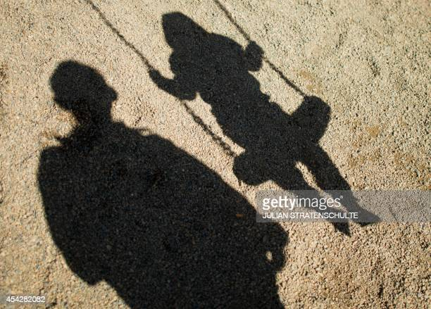 A man and a refugee boy sitting on a swing cast their shadows in the sand of a playground at Lower Saxony's regional refugee office in Braunschweig...