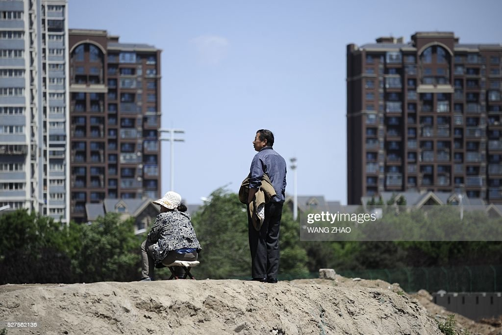 A man and a woman are pictured outside a construction site in Beijing on May 3, 2016. China's economic recovery stabilished in April, an official factory activity gauge showed on May 1, as the property market recovered and credit grew. / AFP / WANG