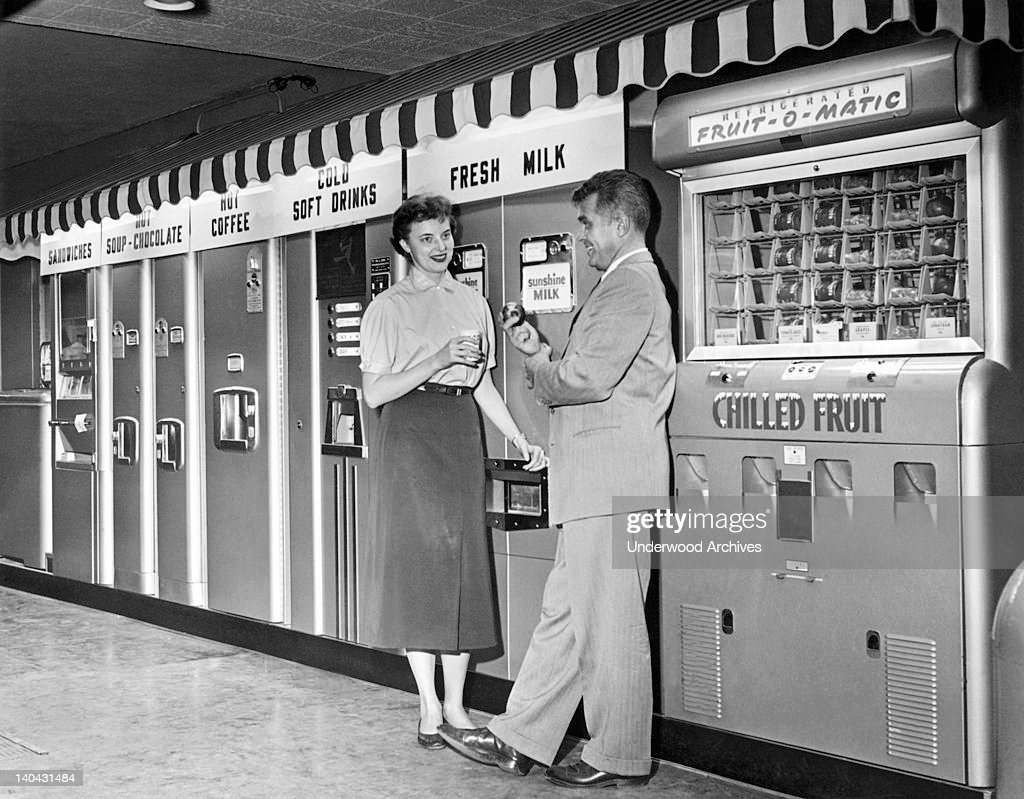 A man and a woman chat and eat by the snack vending machines in a facility, United States, circa 1959.