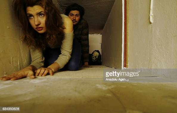 A man and a woman crawl a narrow tunnel in a 'Horror House' established by two entrepreneurs in Antalya Turkey on February 04 2017 Visitors tour...