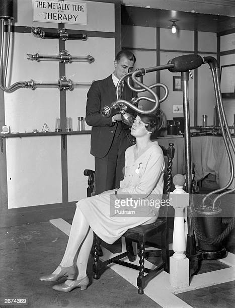 A man and a woman demonstrating medical equipment at a Xray exhibition beside a sign reading 'The Metalix Tube for Therapy'