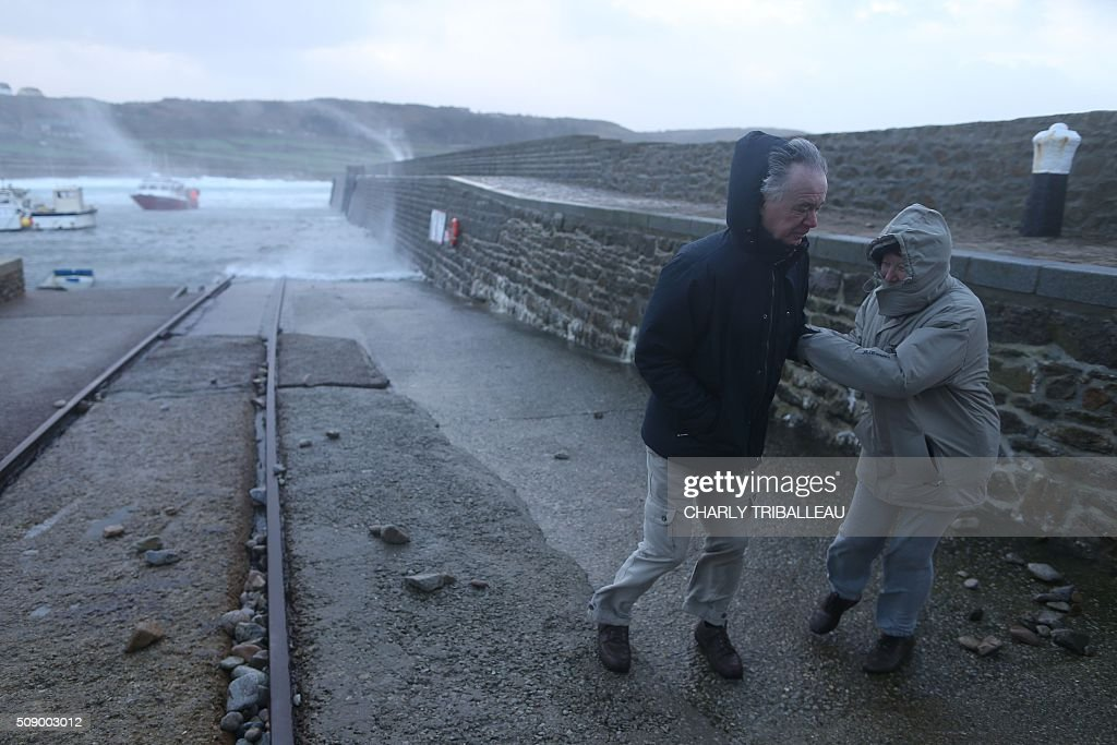 A man and a woman go for a walk in the harbour of Auderville, northwestern France, on February 8, 2016, as strong winds hit the region. Winds of over 130 kh/h were recorded in the region where 16 departments have been placed under alert for wind and flooding waves. / AFP / CHARLY TRIBALLEAU
