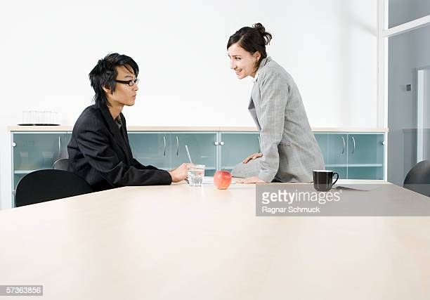 A man and a woman having a discussion in a conference room