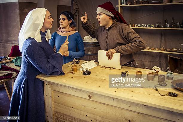 A man and a woman having a heated argument in the apothecary of Diotaiuti Imola Italy mid14th century Historical reenactment