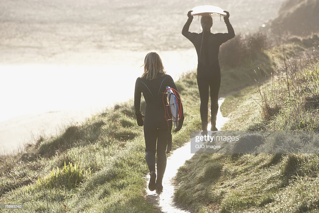 A man and a woman heading down to the surf : Stock Photo