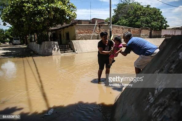 A man and a woman help a girl to pass the floodwaters after a heavy seasonal rainfall caused flood in Sullana Peru on February 21 2017 Peru has been...