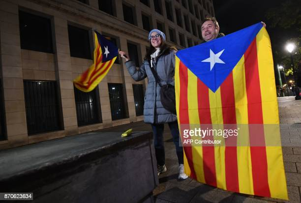 A man and a woman hold the Catalan flag as they stand outside the public prosecutor's office in Brussels on November 5 2017 where a judge will decide...