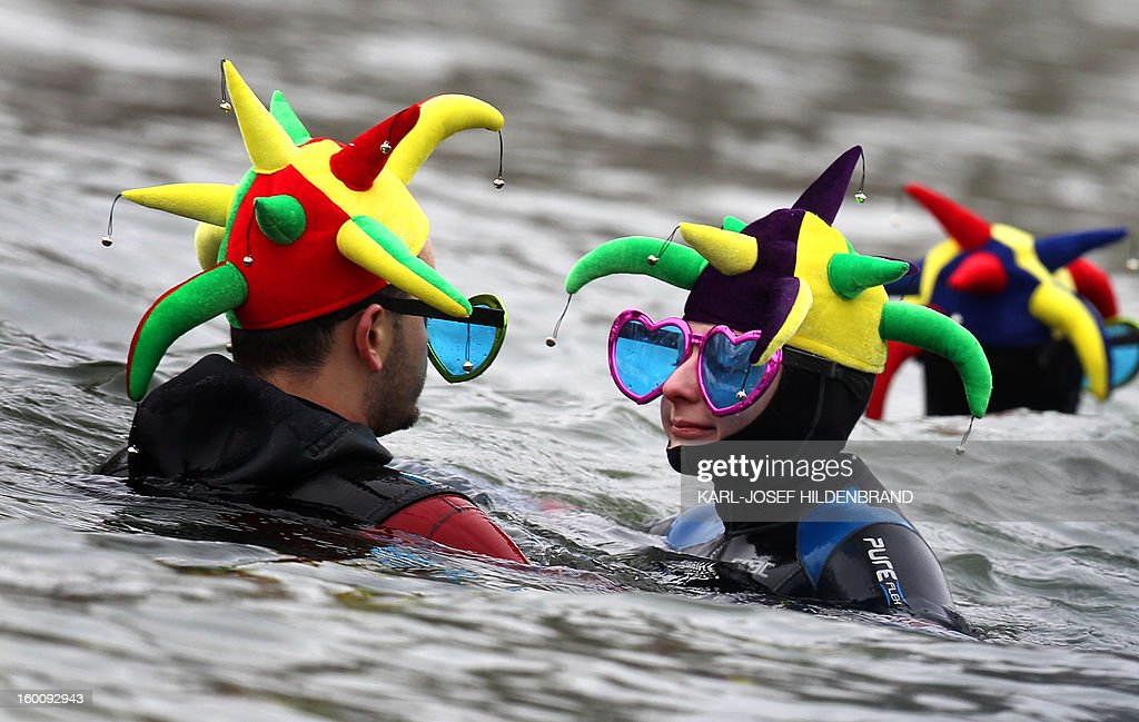 A man and a woman in a wetsuit wear cap and bells and heart shaped goggles as they participate in the 44th traditional Danube winter swimming in Neuburg, southern Germany on January 26, 2013. The nearly 2000 participants swim a distance of 4 km at a water temperature of 3 degree Celsius.
