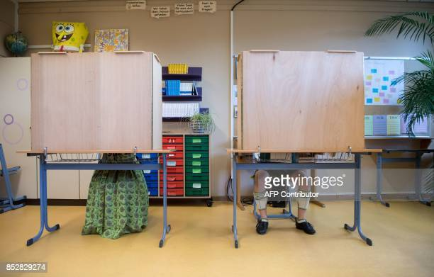 A man and a woman in traditional Bavarian dresses fill out their ballot papers at a polling station in Unterwoessen near Rosenheim southern Germany...