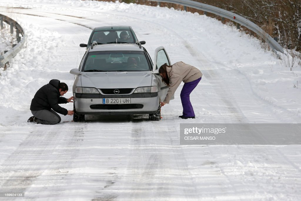 A man and a woman install snow chains on their car to drive on a snow-covered road in Pineda de la Sierra, near Burgos, on January 23, 2013. AFP PHOTO/ CESAR MANSO