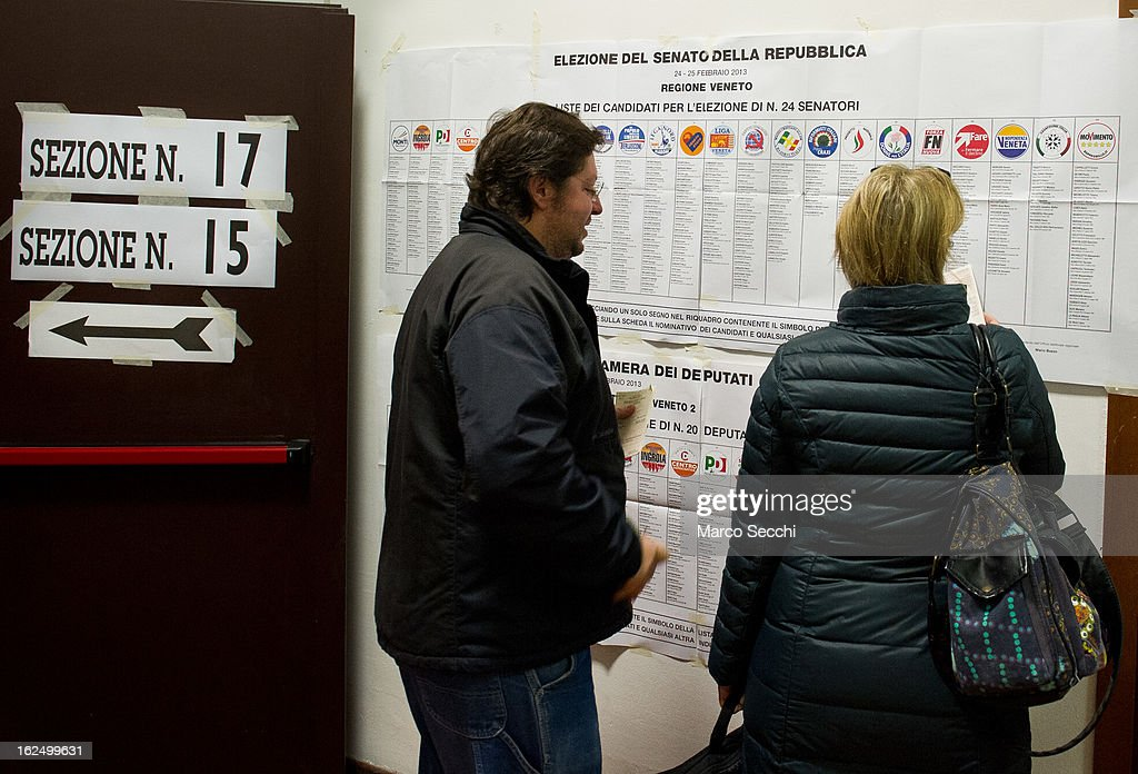 A man and a woman look at an electoral banner before casting their votes as the General Election gets underway on February 24, 2013 in Venice, Italy. Italians are heading to the polls today to vote in the elections, as the country remains in the grip of economic problems . Pier Luigi Bersani's centre-left alliance is believed to be a few points ahead of the centre-right bloc led by ex-Prime Minister Silvio Berlusconi.