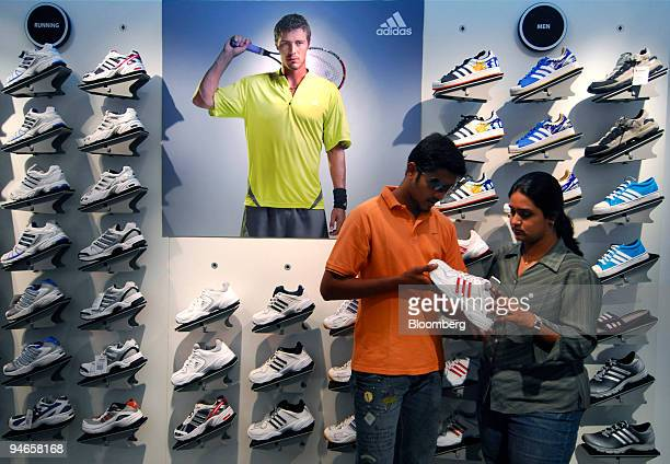A man and a woman look at sneakers manufactured by Adidas at a mall in Mumbai India on Thursday Nov 29 2007 India's economy grew last quarter at the...