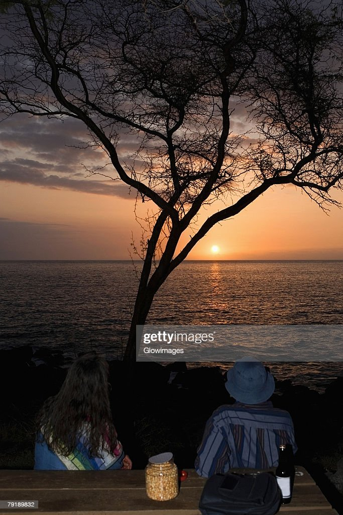 Man and a woman looking at sunset over the sea, Pakini Nui Wind Project, South Point, Big Island, Hawaii Islands, USA : Foto de stock