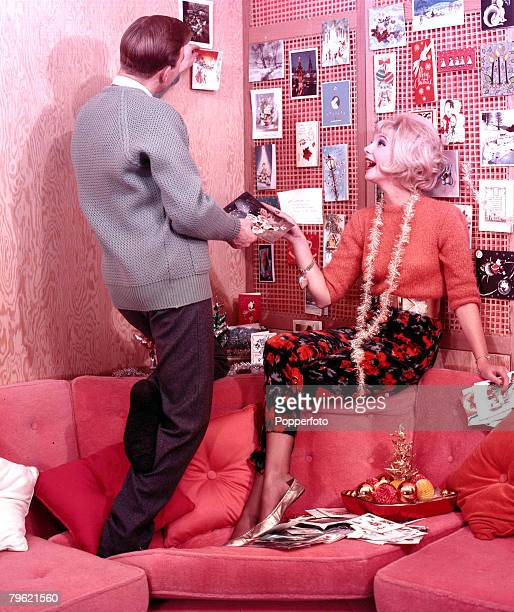 1960 A man and a woman on a sofa laughing together wearing fashionable clothing whilst pinning up postcards on the wall the woman also has a piece of...