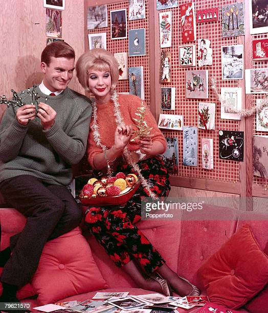 1960 A man and a woman on a sofa smiling together wearing fashionable clothing whilst playing with christmas decorations the woman also has a piece...