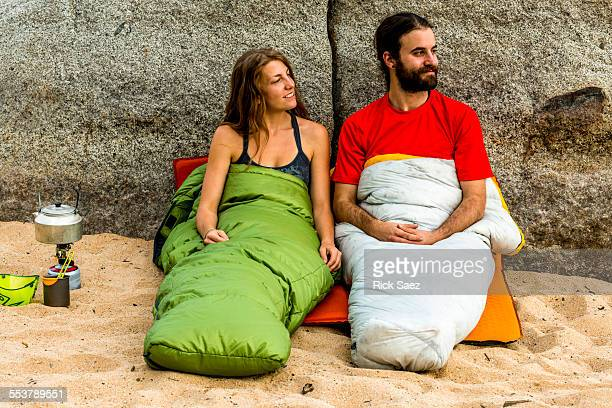 Man and a woman on the beach in sleeping bags smiling