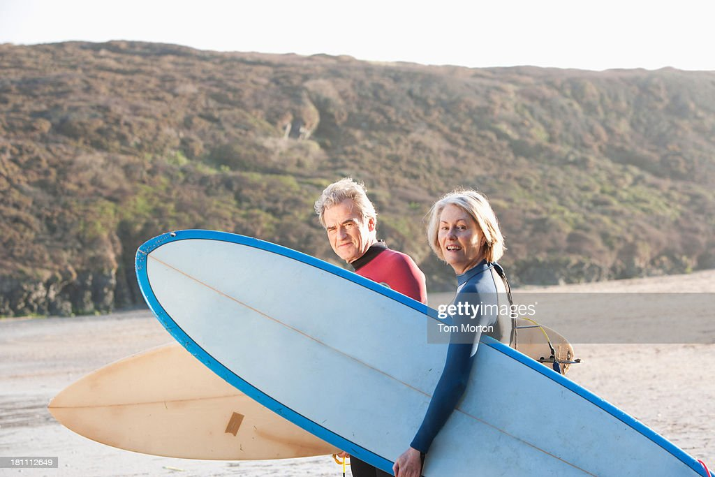 A man and a woman on the beach with surfboards : Stock Photo