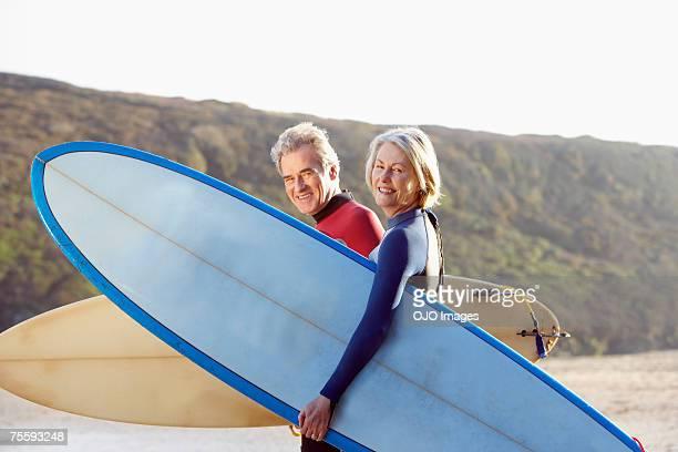Un homme et une femme sur la plage avec des planches de surf