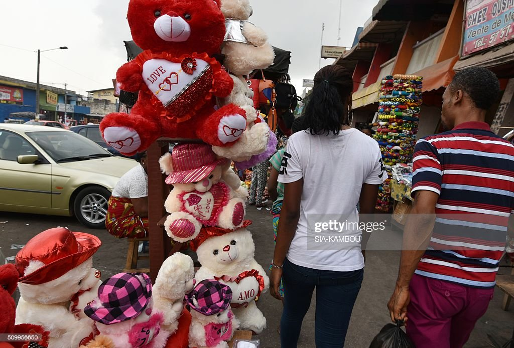 A man and a woman pass near Valentine's day items for sale on February 13, 2016 in a street market in Marcory, a popular suburb of the Ivorian capital. / AFP / SIA-KAMBOU