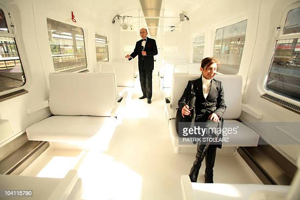 A man and a woman pose inside a white designed carriage in a 'SBahn' commuter train painted outside in gold colour at the station of Oberhausen...