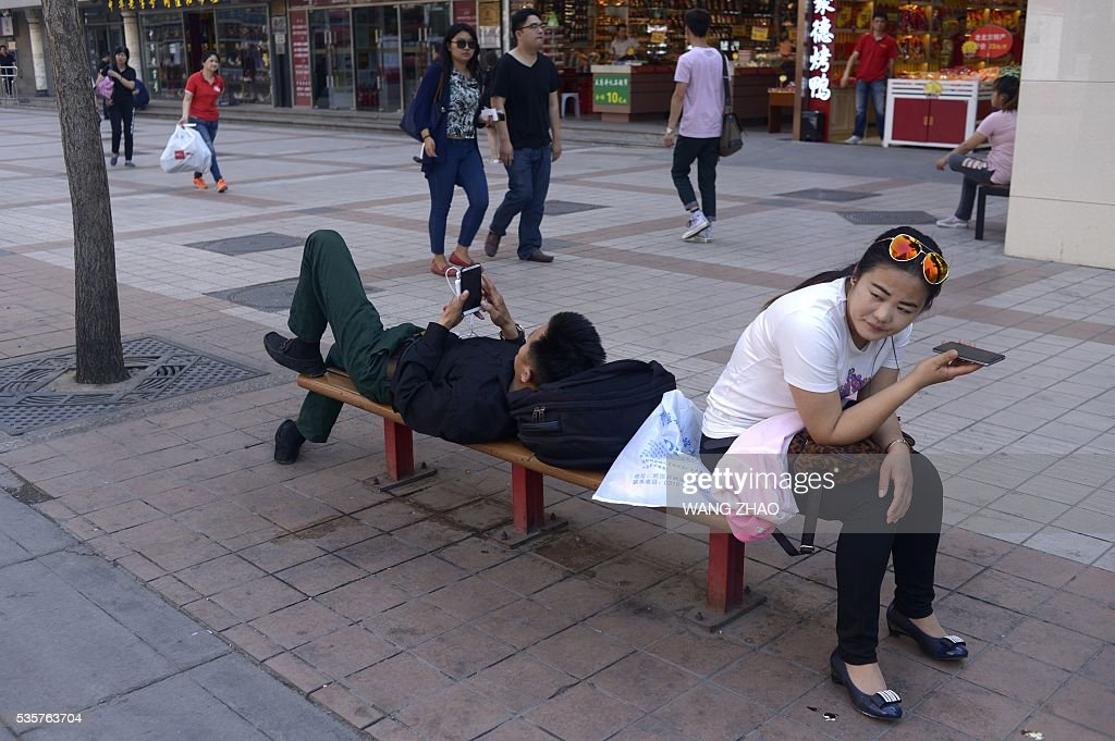 A man and a woman rest on a bench as they use their mobile phones in Beijing on May 30, 2016. / AFP / WANG