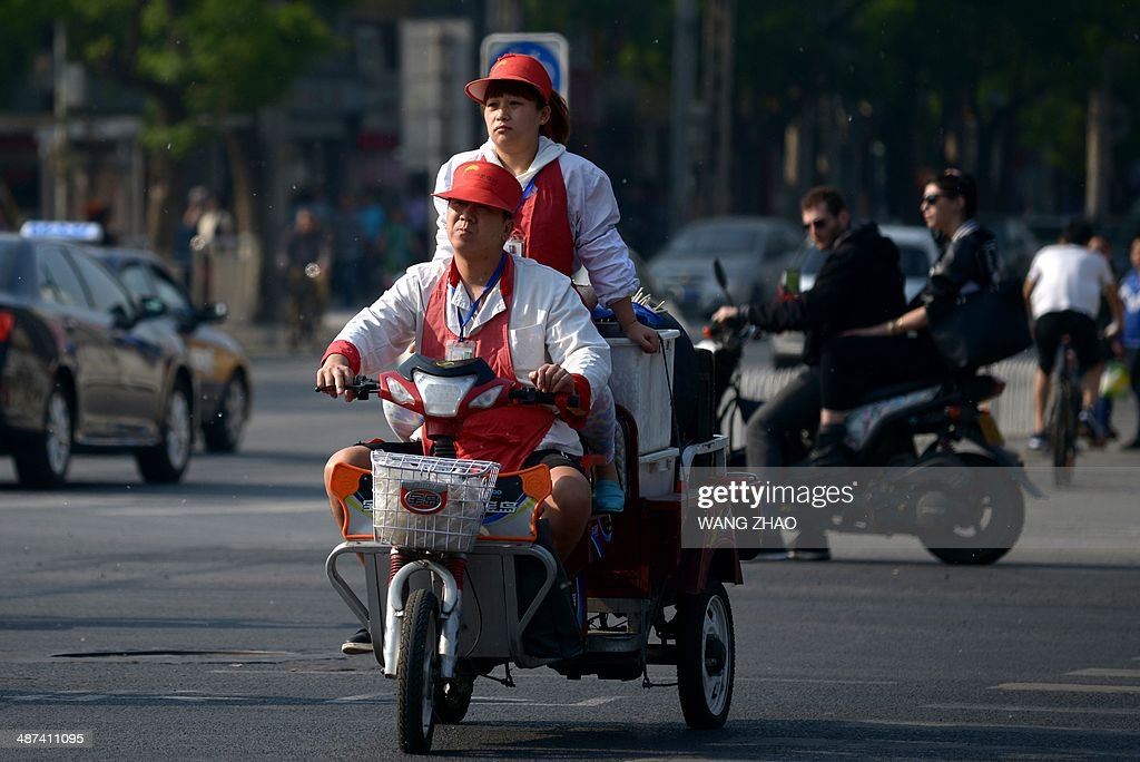 A man and a woman ride a motorized tricycle at an intersection in Beijing on April 30, 2014. Chinese manufacturing activity improved slightly in April as domestic demand showed 'mild improvement', it was reported on April 23, but it warned the world's second-largest economy was still showing signs of weakness.