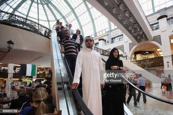 A man and a woman ride an escalator in the huge shopping complex 'Mall of the Emirates' on December 3 2009 in Dubai United Arab Emirates Stock...