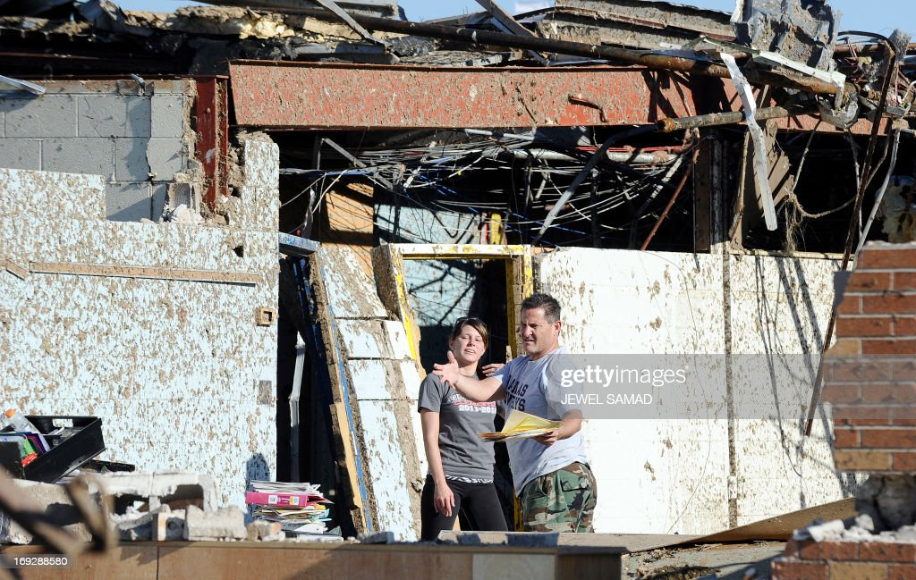 A man and a woman search throung debris at tornado devastated Plaza Towers Elementary School on May 22, 2013 in Moore, Oklahoma. Seven children died in the school during the tornado. As rescue efforts in Oklahoma wound down, residents turned to the daunting task of rebuilding a US heartland community shattered by a vast tornado that killed at least 24 people. The epic twister, two miles (three kilometers) across, flattened block after block of homes as it struck mid-afternoon on May 20, hurling cars through the air, downing power lines and setting off localized fires in a 45-minute rampage. AFP PHOTO/Jewel Samad