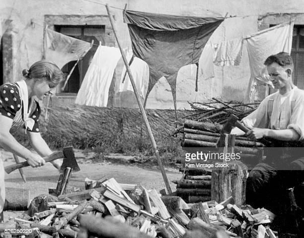 A man and a woman share the duties splitting wood in their backyard by the hanging laundry