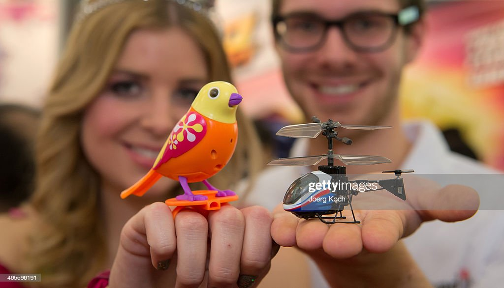 A man and a woman show the world's smallest I/R model helicopter called 'Nano Falcon' and a small interactive bird called 'DigiBirds' at the Silverlit exhibition stand during the Press-Preview of the Nuremberg International Toy Fair 2014 (Nuernberger Spielwarenmesse) on January 28, 2014 in Nuremberg, Germany. The Nuremberg International Toy Fair 2014 is the worlds biggest toy fair and is opendend to visitors from January 29 to February 3.