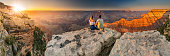 This is a photograph of a man and a woman sit at the edge of the Grand Canyon at sunset minutes