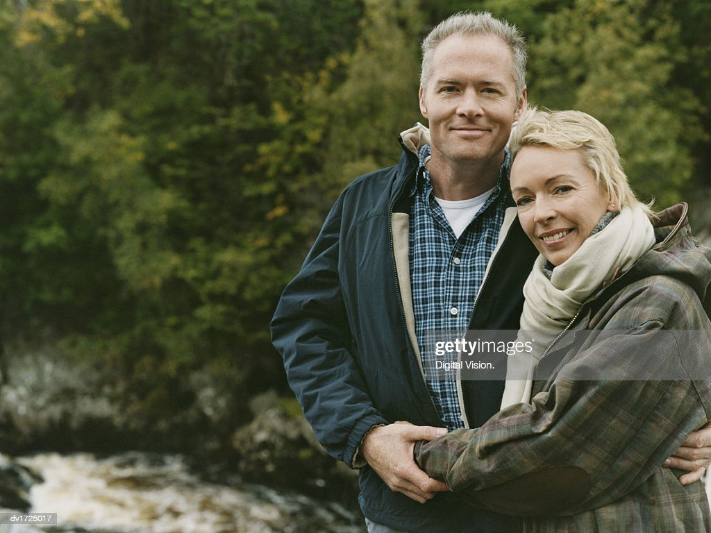 Man and a Woman Stand by a River With Their Arms Around Each Other : Stock Photo