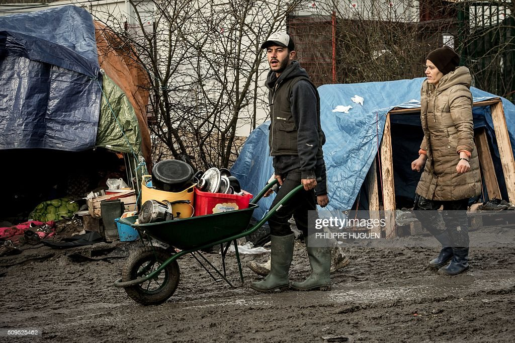A man and a woman walk in the so-called 'Jungle' migrant camp in Gande-Synthe where 2,500 refugees from Kurdistan, Iraq and Syria live on February 11, 2016 in Grande-Synthe near the city of Dunkirk, northern France. / AFP / PHILIPPE HUGUEN