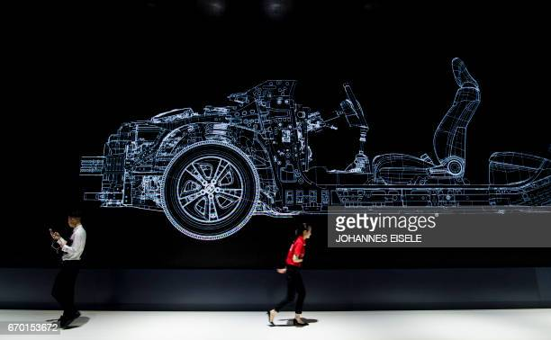 A man and a woman walk under an advertisement for Japanese carmaker Toyota during the first day of the 17th Shanghai International Automobile...